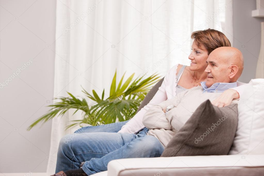 Mature couple watching tv on the sofa — Stock Photo