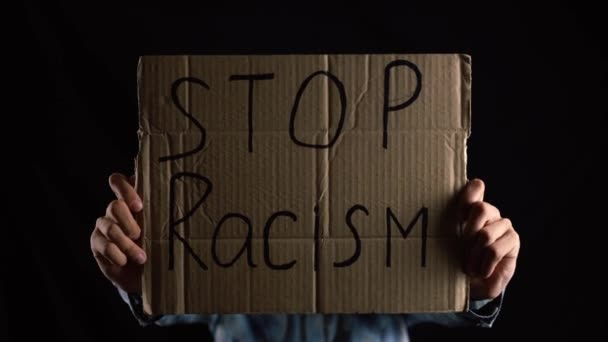 Kaukasier hält Karton mit der Aufschrift STOP Racism.