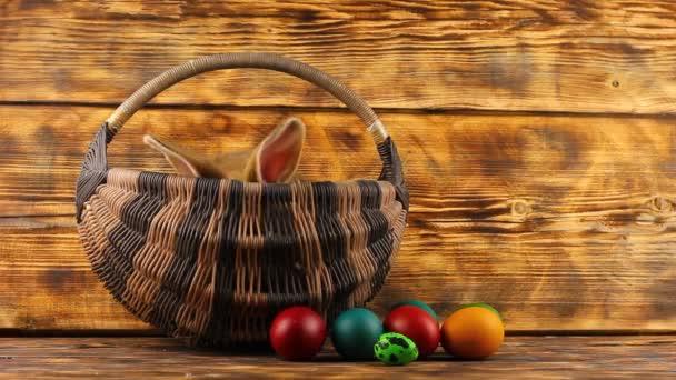 malý hnědý nadýchaný roztomilý králík sedí v proutěném koši s multi-barevné rozmanité velikonoční vejce