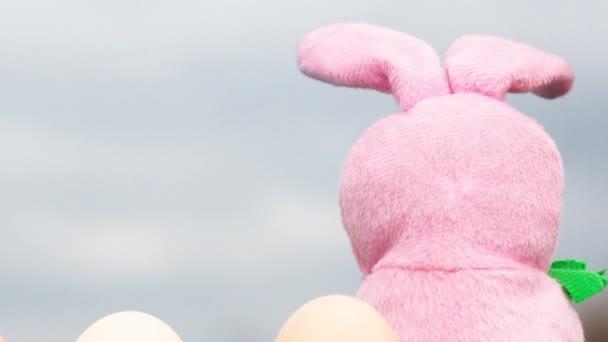 Lassított 4k. Kis rózsaszín plüss húsvéti nyuszi ül a csirke tojás.