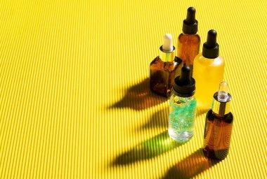 Cosmetics liquid gel serum oil hyaluronic acid bottles dropper bright yellow background. Research cosmetics laboratory