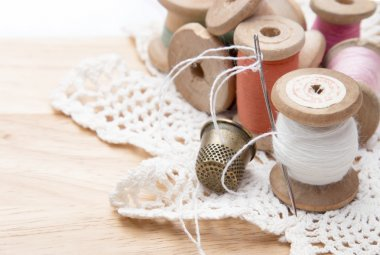 cotton thread for sewing, wound on a wooden spool, white lace and a metal thimble, vintage, on wooden background