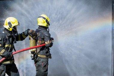 İki itfaiyeci ya da itfaiyeci su püskürtmek için birbirlerine yardım ederler. Perde şekli ve gökkuşağı refleksi su püskürtüsünde, içinde ateş bulunan konteynerin önünde..