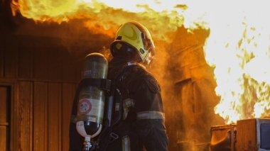 Koruyucu takım elbiseli itfaiyecinin arkası antrenman sırasında mutfak duvarındaki yangına bakın ya da hazırlık için personel alın ve profesyonel olarak çalışmaya hazır olun..