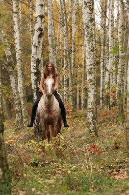 Pretty young girl riding a horse without any equipment in autumn
