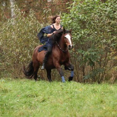 Nice girl riding a horse without bridle or saddle