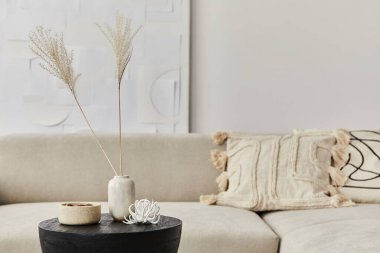 Stylish composition at fancy interior with wooden black coffee table, dried flowers in vase, pillow, blanket in modern home decor. Details. Template.