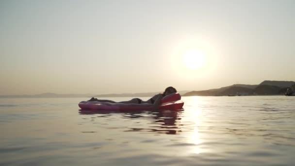 Dlouhý záběr dívky ležící na nafukovací matraci v moři a sledující západ slunce.