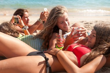 Adolescents texting on sand