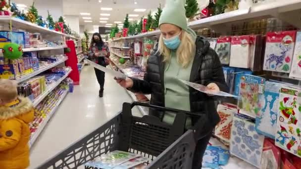 Europe, Kiev, Ukraine - November 2020: Masked girl with a grocery cart buys Christmas decorations in one of the city's supermarkets during the Covid-19 coronavirus pandemic. Showcase with New Year's t