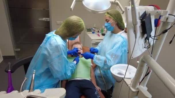 Kyjev, Ukrajina - srpen 2021: Zubař léčí dětské zuby. Zubař v práci. Zubní ordinace.
