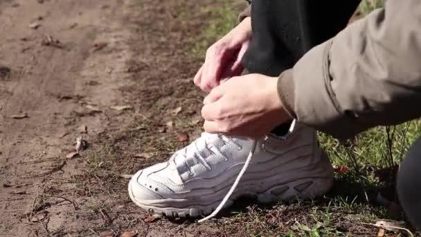 Mädchen schnüren Schnürsenkel an Turnschuhen auf der Straße am Herbstnachmittag in der Sonne