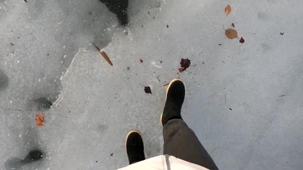 Mädchen in schwarzen Stiefeln läuft im Winter auf eisglatter Straße in Nahaufnahme