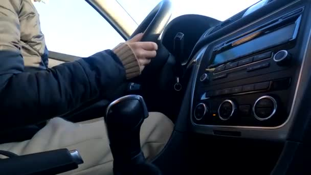 Girl driving her car in motion close-up, hands on the steering wheel