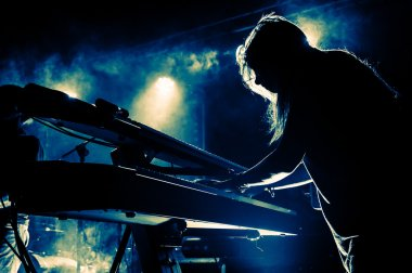 Girl playing keyboards during concert, silhouette with backlight