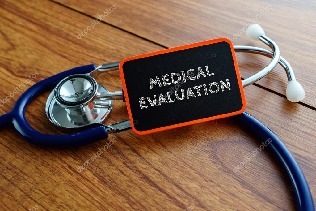 Word Medical Evaluation With Stethoscope On Wooden Table  Stock