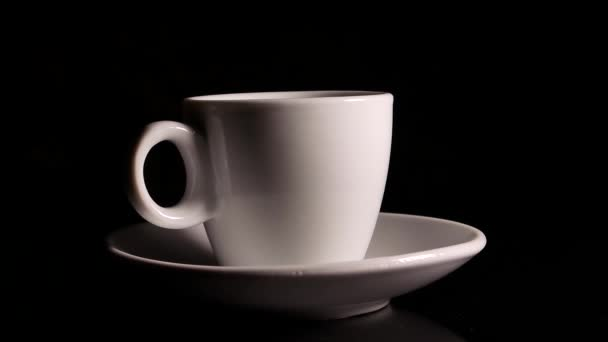 Ceramic coffee cup rotates on a black background. Cup and saucer. Ceramic tableware. Coffee house. Cafe. Kitchenware. Hot drink. Black background. Rotation in a circle. Video.