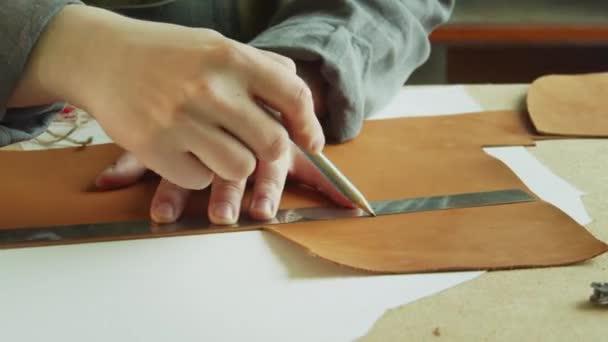 Egy cipész rajzol egy vonalat egy ceruzával egy nagy darab valódi bőrre, hogy levágja. Az exkluzív cipők létrehozásának folyamata.