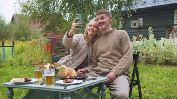Newlyweds spend their honeymoon in the country, photographed on a smartphone for memory against background of their home