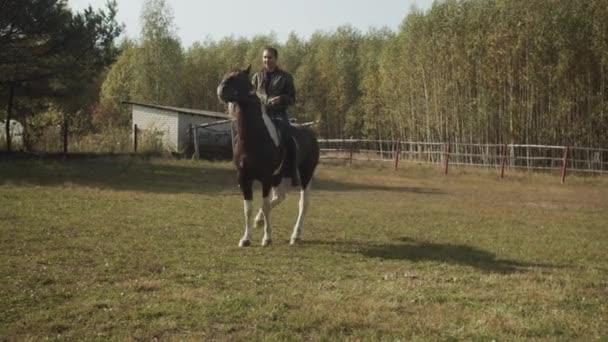 Eine junge Studentin einer Reitschule trainiert auf einer Koppel unter freiem Himmel und reitet auf einem gefleckten Pferd. In Zeitlupe