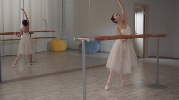 Graceful ballerina girl in the dance hall makes beautiful bends in front of the mirror