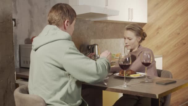 Husband and wife at the table in the kitchen have fun talking and drinking red wine from glasses. Festive dinner on a memorable date.
