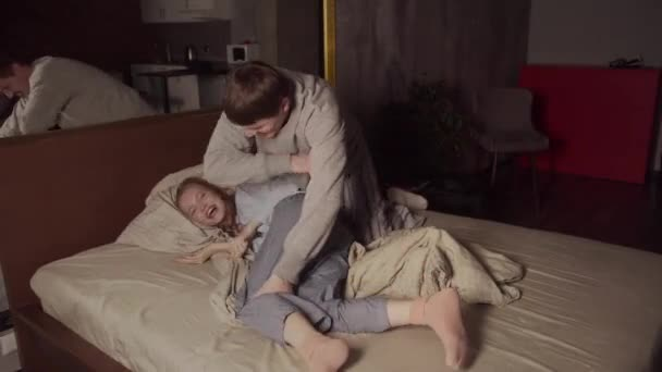 Mladý manžel se poflakuje se svou ženou v posteli, hádají se polštáři, jemně ji plácá dlaní do zadku.