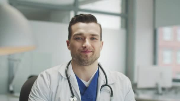 A young doctor with a positive smile looks directly at the camera. Close-up portrait in the medical office of the hotel.