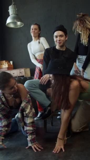 Mädchen tanzen und zappeln um den Kerl herum, während er auf einem Stuhl sitzt