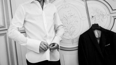 man buttons white shirt