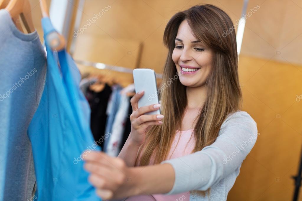 8ed0b88f3c9efc Vrouw met behulp van mobiele telefoon in kleding winkel — Stockfoto ...