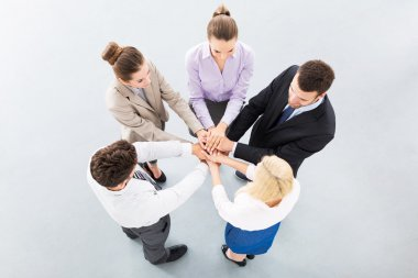 Young business people joining hands in circle