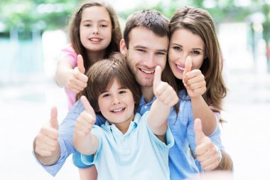 Happy young family thumbs up