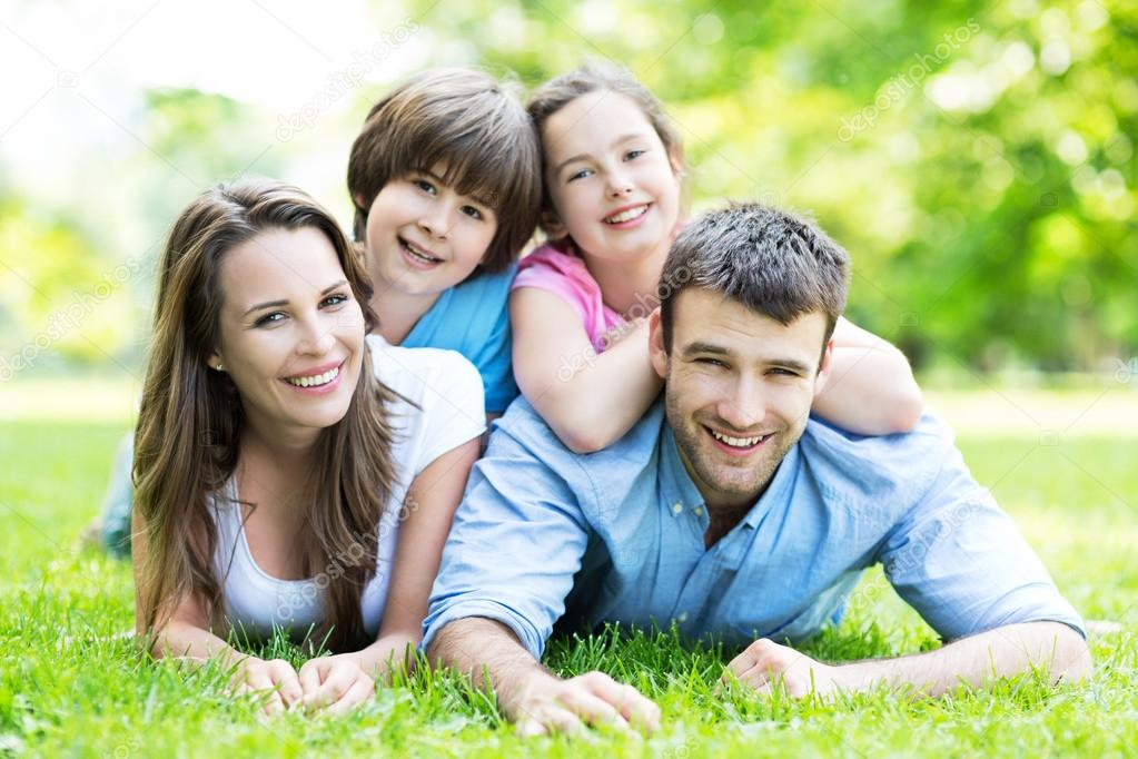 Happy young family lying on grass