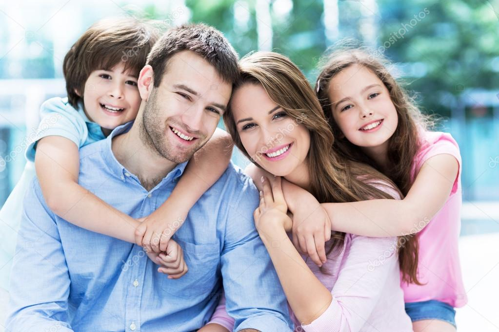 808e180a6f1 Happy young family hugging — Stock Photo © pikselstock  76181397