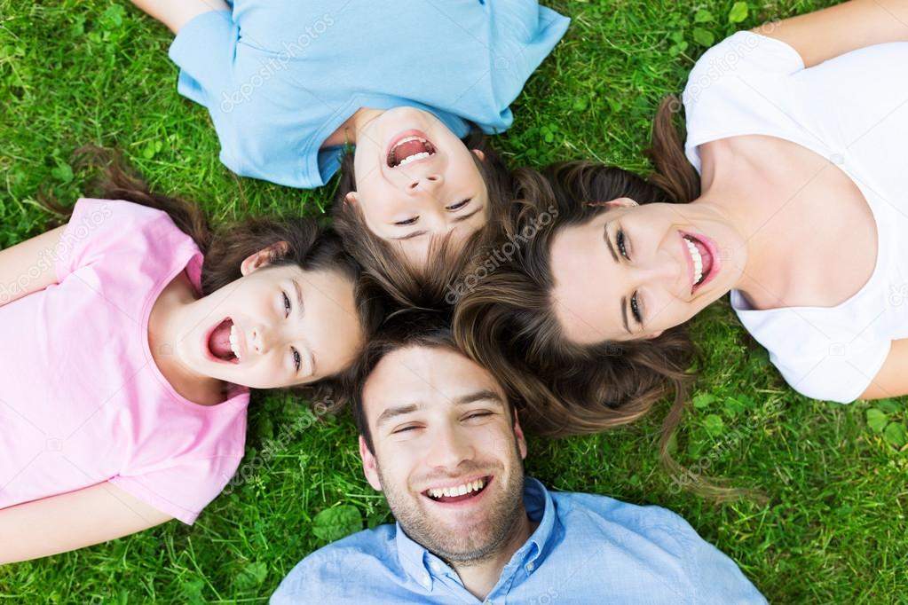 Happy family on grass, top view