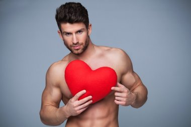 Muscular man holding heart shape