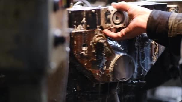 Továrna na výrobu náhradních dílů pro automobily a traktory. Souhrnný obráběcí stroj. Pracovník vloží hliníkový sochor pro zpracování. Detailní záběr.