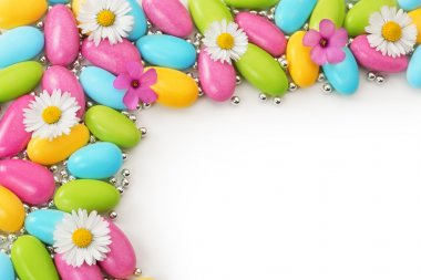 Multicolored dragees and wildflowers on white background