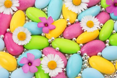 Heap of colored sugar coated almonds and wildflowers