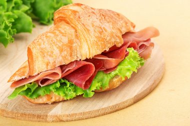 Croissant filled with ham and lettuce on wooden chopping board