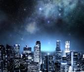 Panorama města v noci pod hvězdnou oblohou