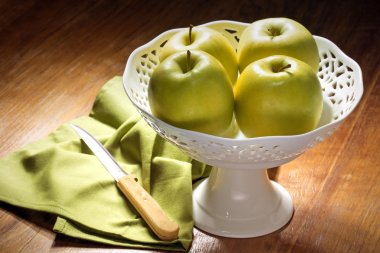 Four green apples in a china centerpiece on wooden table