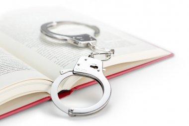 close up of steel handcuffs over an open book