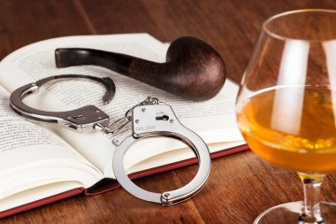glass of liquor, handcuffs and pipe on open book