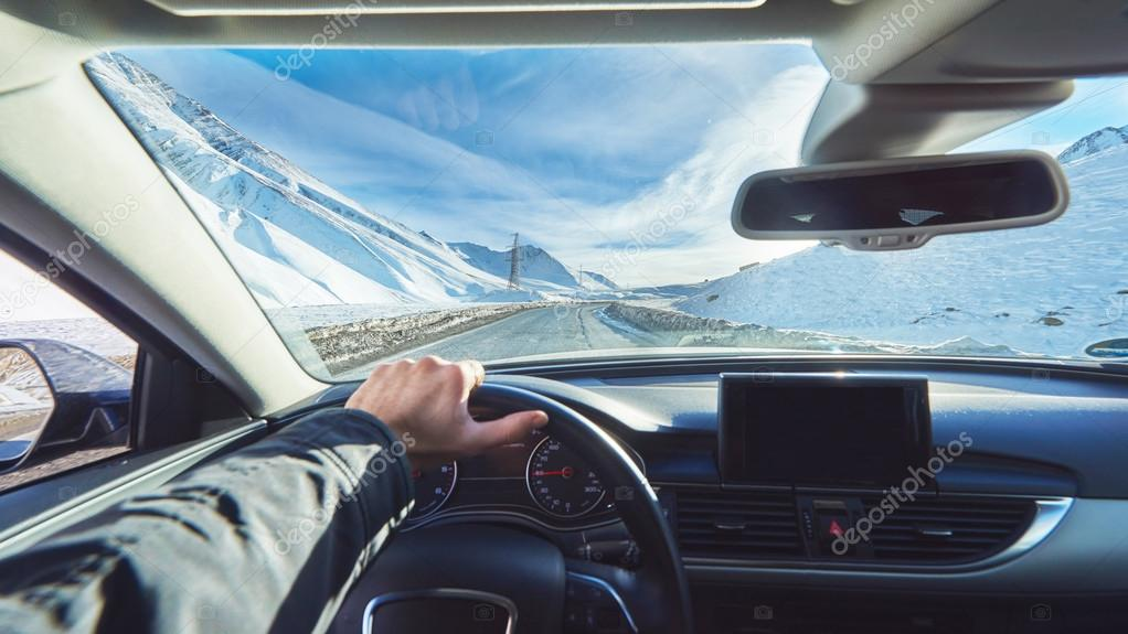 snowy mountains road view from the modern luxury car interior with drivers hand on steering wheel with gps navigation mockup