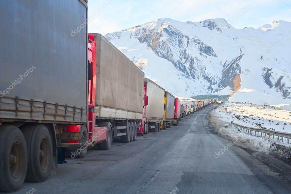 trucks with turkish cargo waiting on a road curve in front of the russian border
