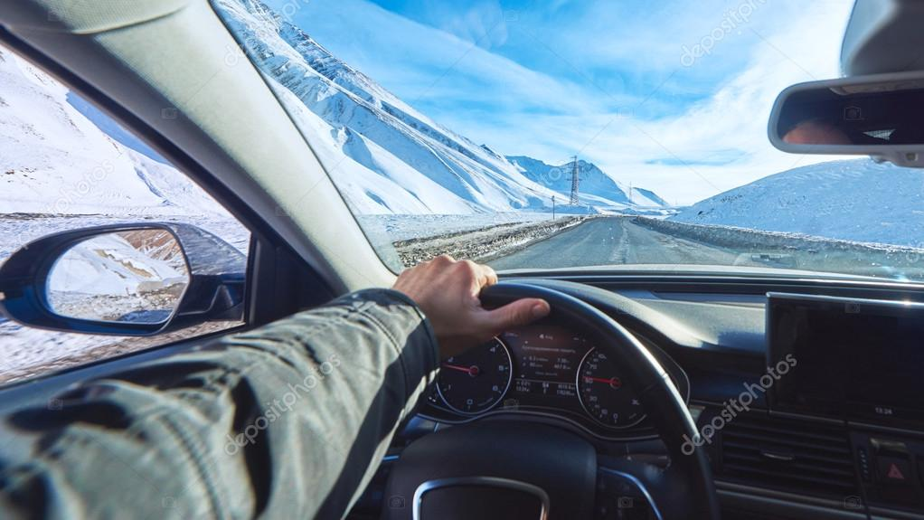 snowy mountains road view from the modern luxury car interior with drivers hand on steering wheel