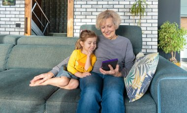 Grandmother and granddaughter spend time together and read fairy tales and stories on an e-book or tablet. Warm family relationship. Taking care of grandparents. The nanny plays with the child.