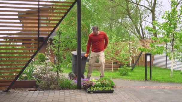Der Hausbesitzer holt zu Beginn des Frühjahrsregens einen Mülleimer heraus.